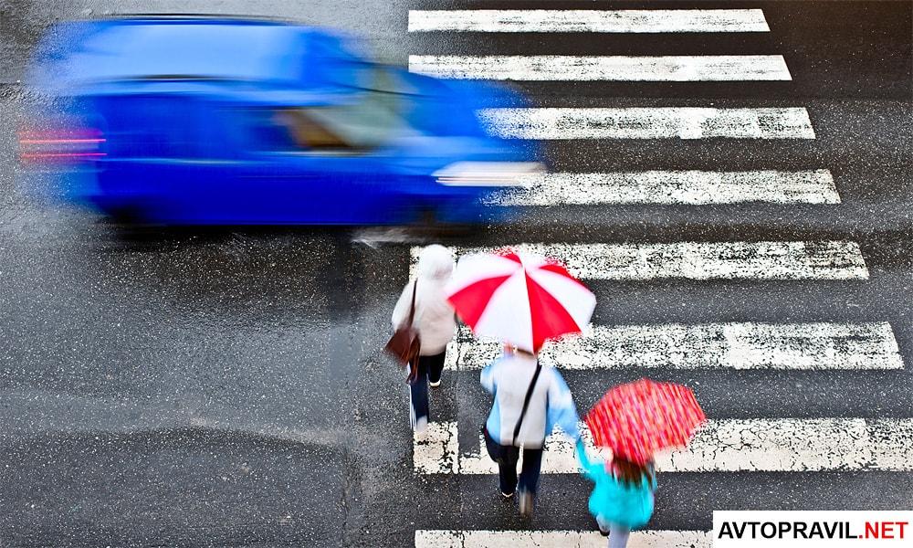 Пешеходы идущие на пешеходном переходе и быстро движущаяся машина