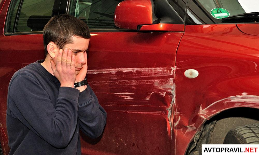 Мужчина сидящий возле разбитой машины