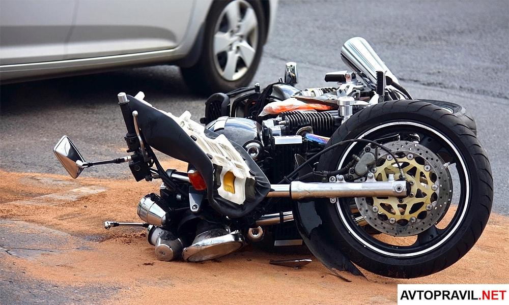 Разбитый в ДТП мотоцикл лежащий на дороге