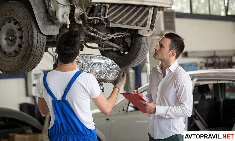 Механик и оценщик разбирающие автомобиль