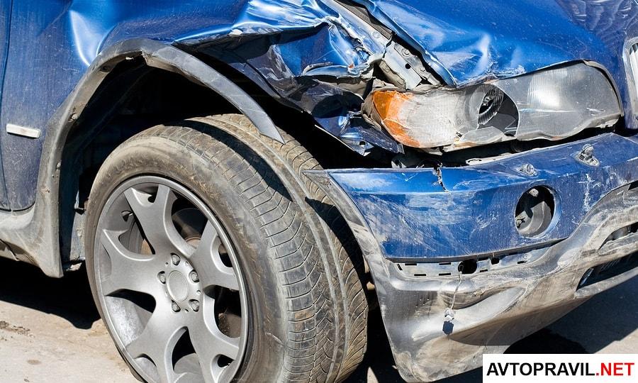 Синий автомобиль с разбитой фарой после аварии