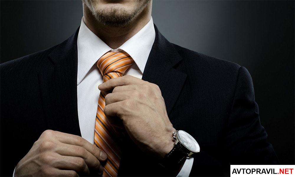 Мужчина попрпавляющий галстук