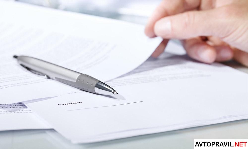 Документы и ручка, лежащие на столе