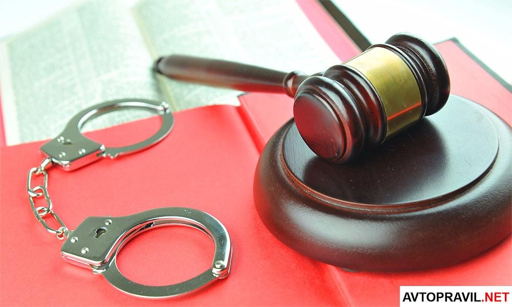 Судейский молоток, наручники и документы лежащие на столе