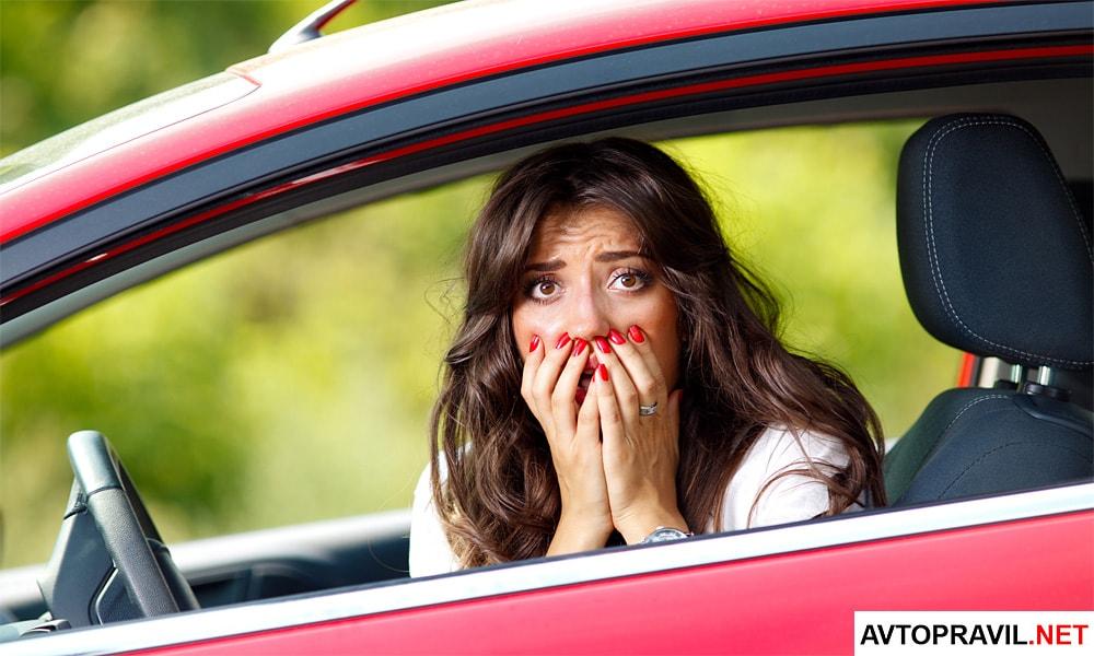 Испуганная девушка сидящая за рулем автомобиля