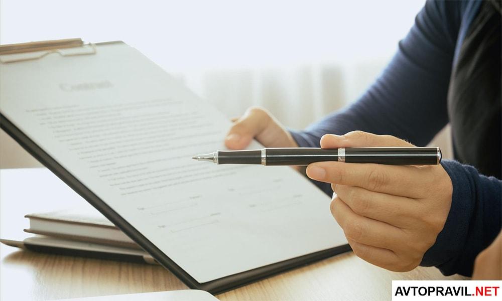 Мужская рука держащая ручку и документ