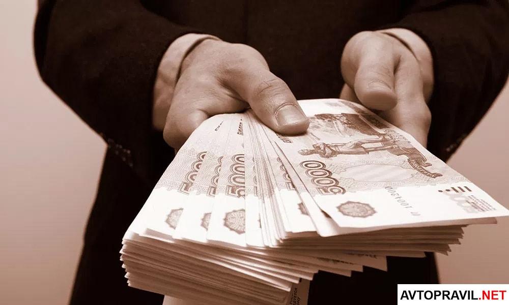 Мужчина держащий стопку рублей