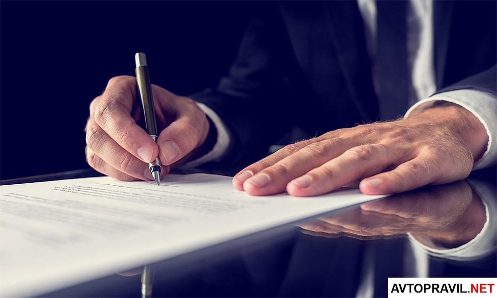 Мужчина за столом, заполняющий документы