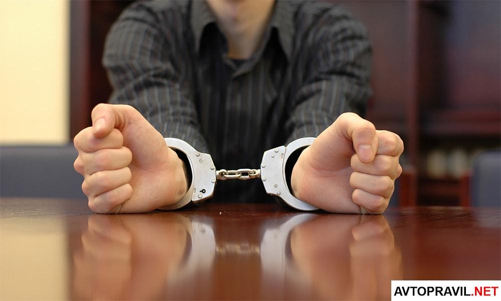 Мужчина в наручниках, сидящий за столом