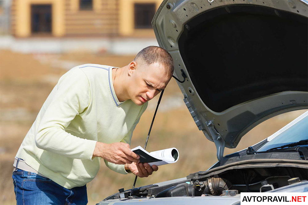 Мужчина рассматривающий документы возле автомобиля