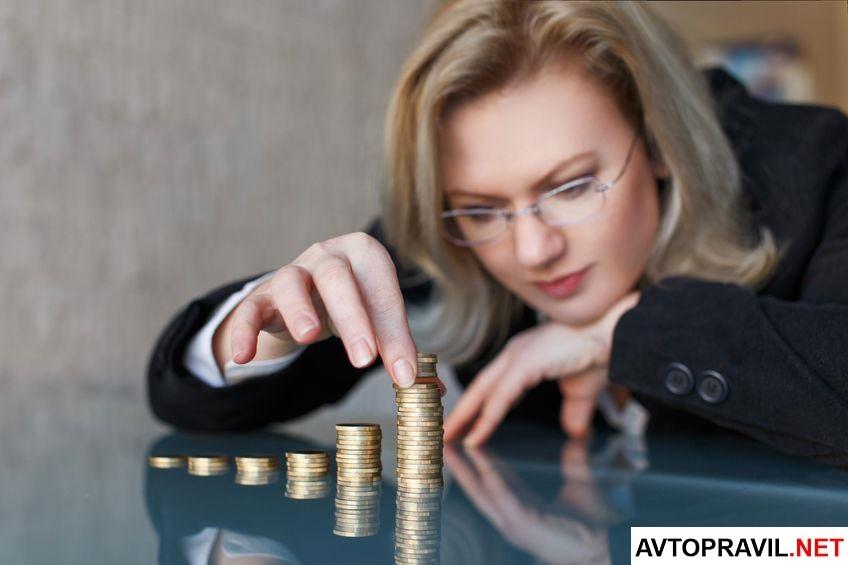 Женщина складывающая монетки в стопки