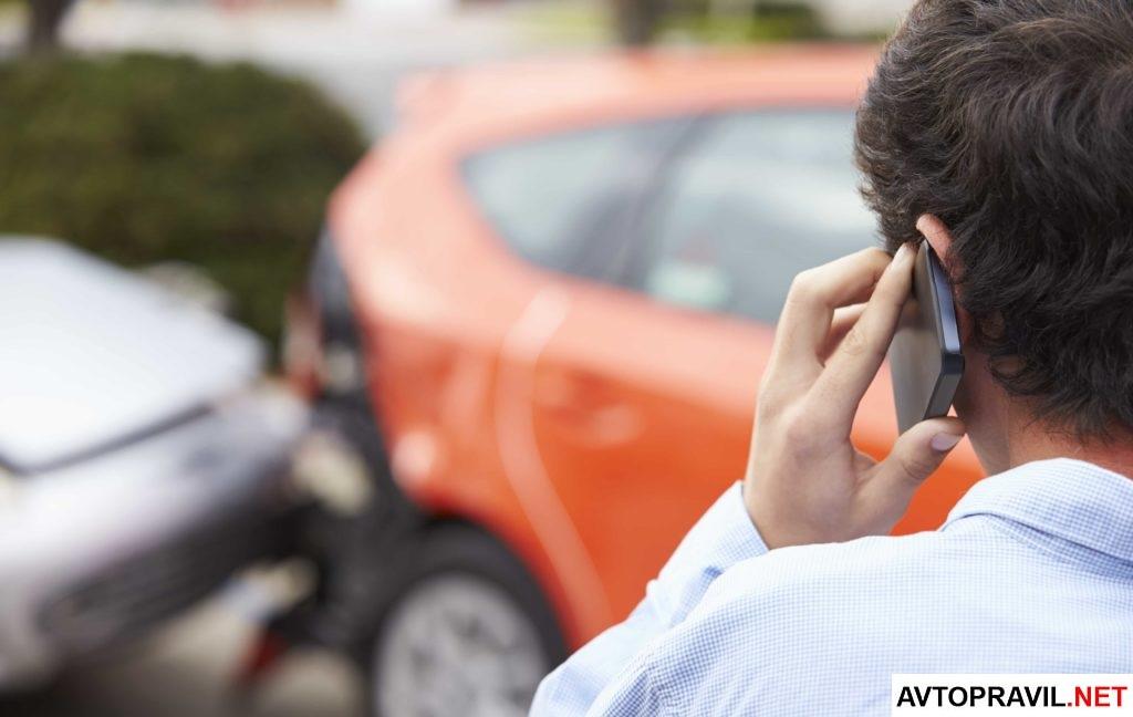 Мужчина звонящий по телефону после ДТП