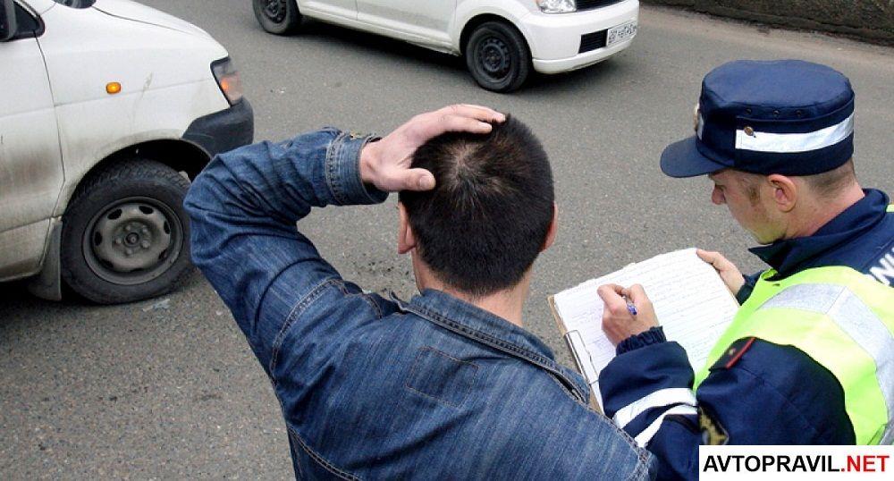 Виновник ДТП стоящий с инспектором возле машин