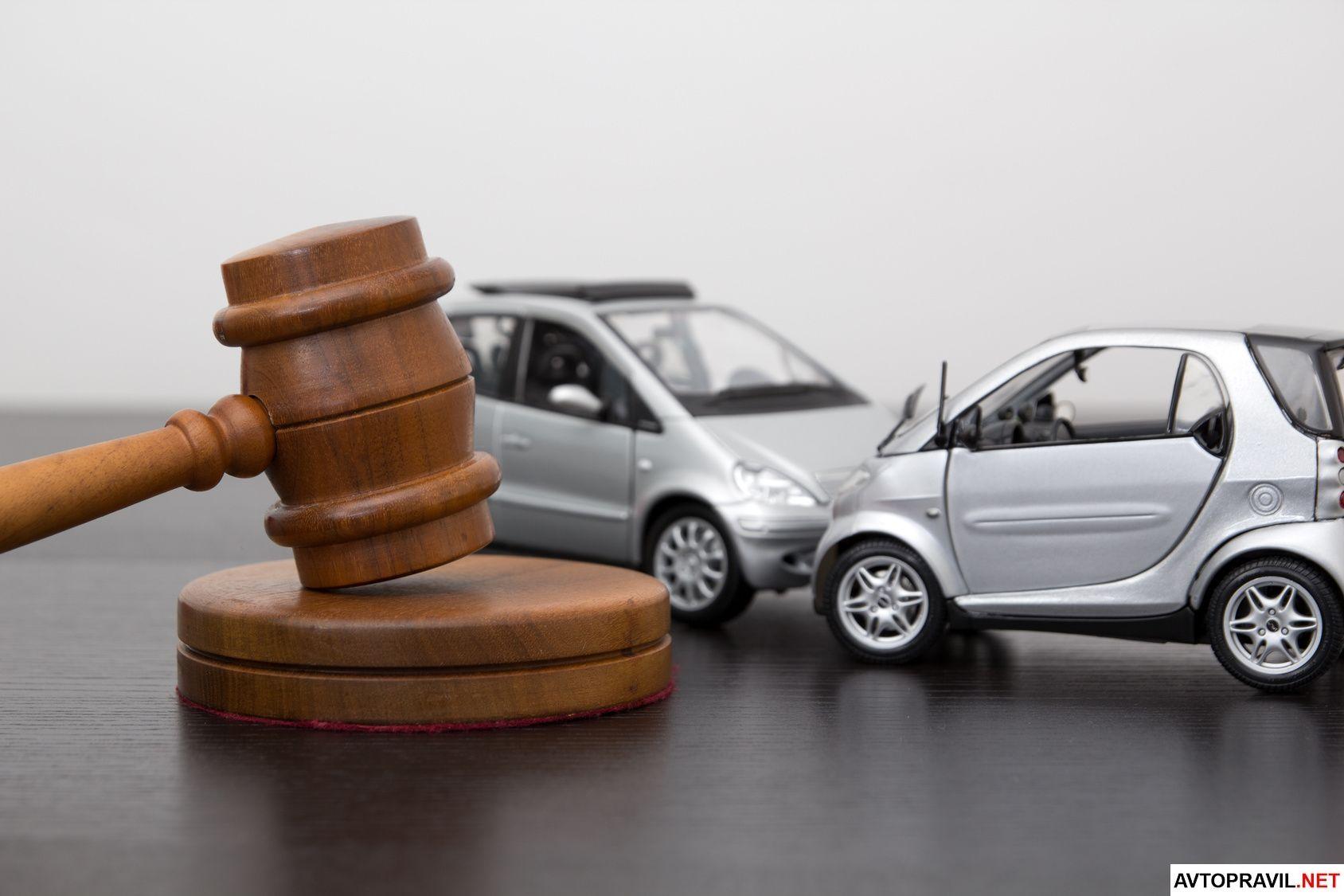 Судебный молоток и игрушечные модели двух автомобилей
