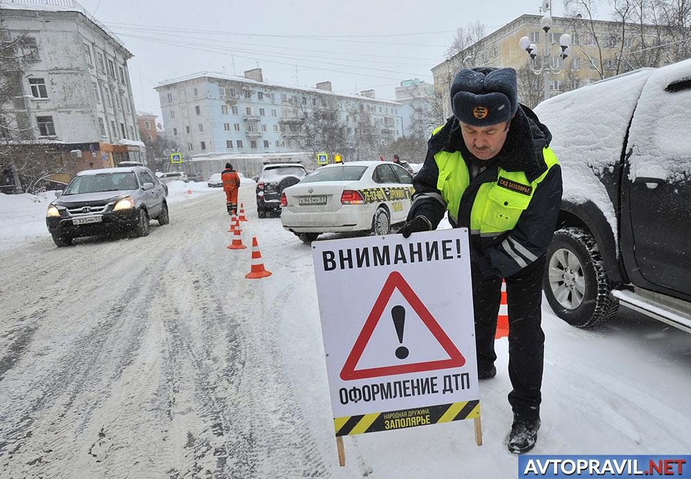 Инспектор ГИБДД, выставляющий табличку посреди дороги