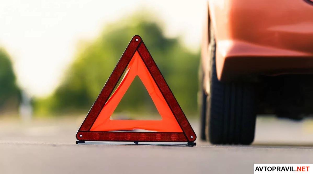 Знак аварийной остановки и машина на дороге