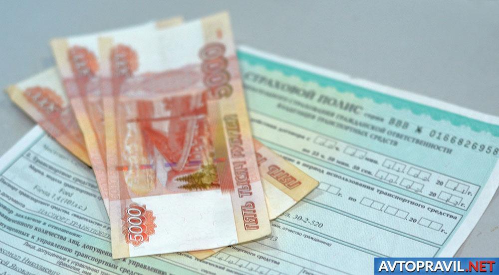 Рубли и страховой полис, лежащие на столе