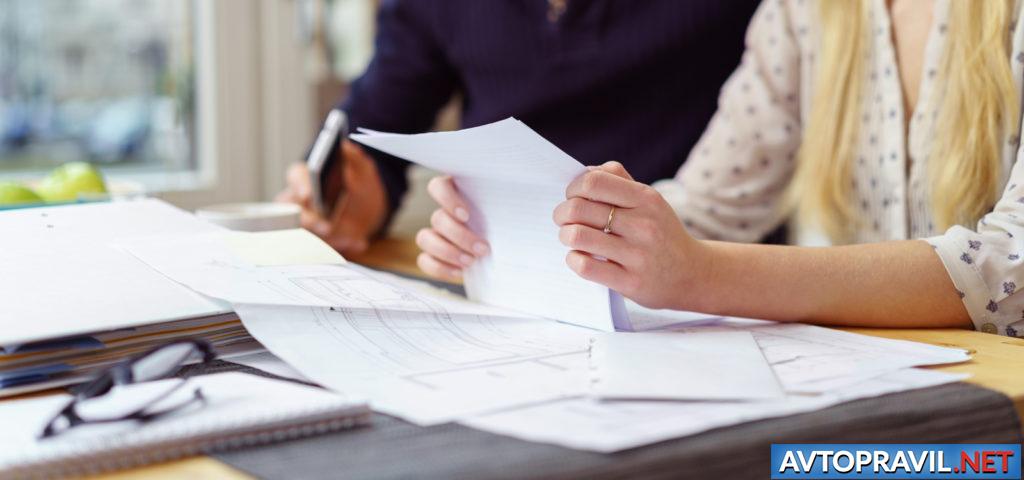 Девушка держащая документы над столом