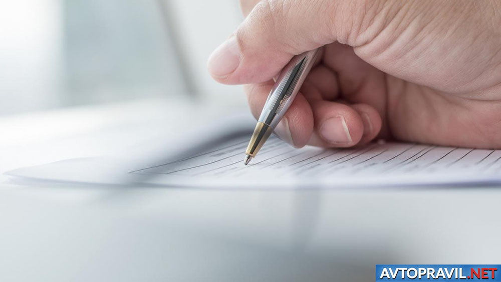 Мужская рука, пишущая на листе бумаги