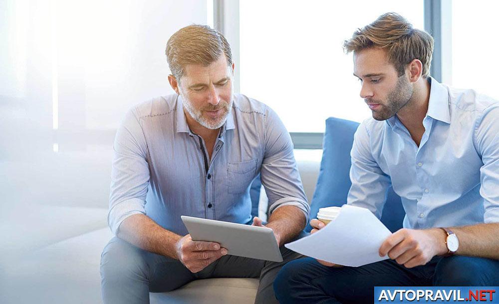 Двое мужчин, сидящих с планшетом в руках