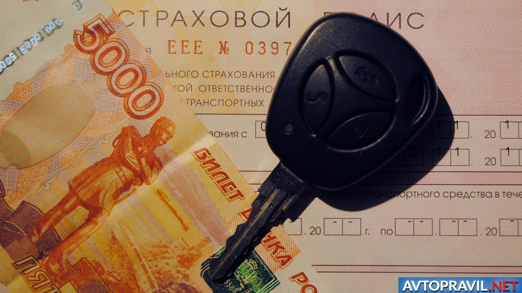 Ключ от авто на страховом полисе и денежной купюре