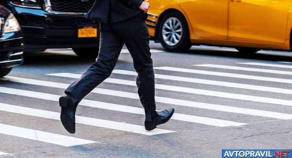 Мужчина, перебегающий дорогу по пешеходному переходу