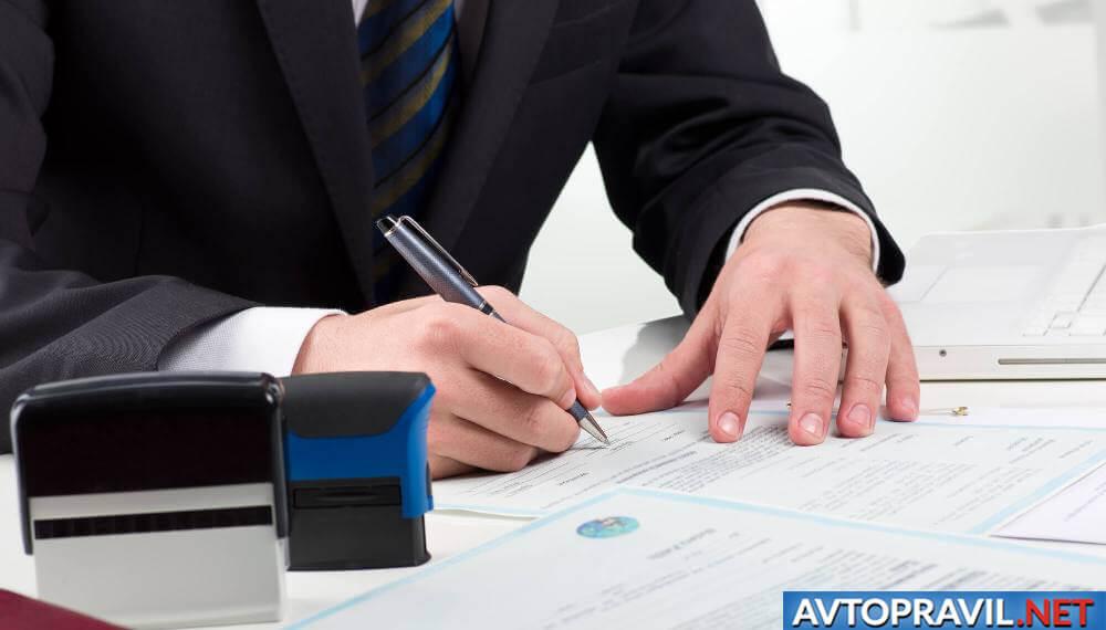 Мужчина, подписывающий документы на столе
