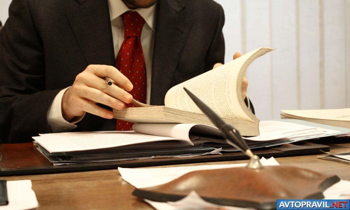 Мужчина в красном галстуке, сидящий за рабочим столом
