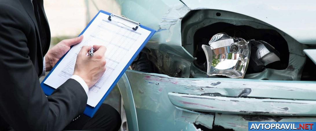 Мужчина заполняющий документы возле авто после ДТП