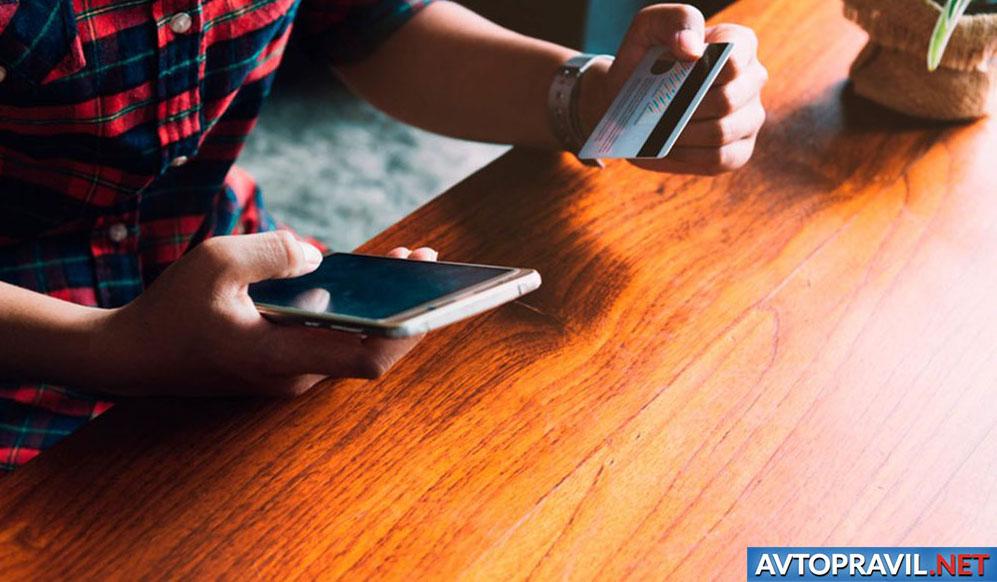 Парень, оплачивающий услугу через мобильный телефон