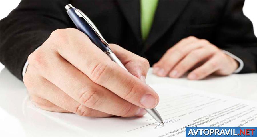 Рука с ручкой над документами