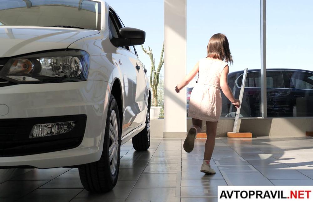 Играющий ребенок возле автомобиля