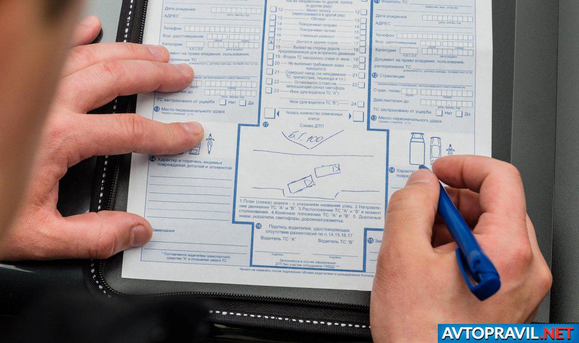 Мужская рука с ручкой над схемой ДТП в Евпропротоколе