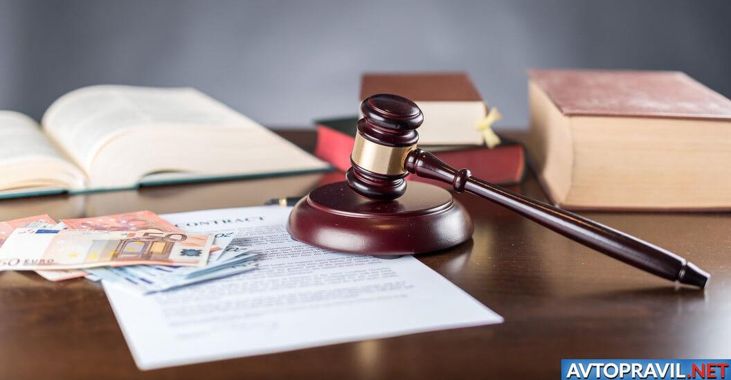 Судейский молоток и деньги, лежащие на документах