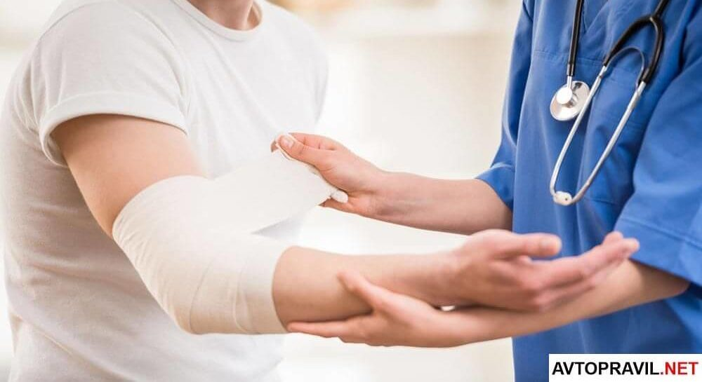Врач, перебинтовывающий руку пациенту