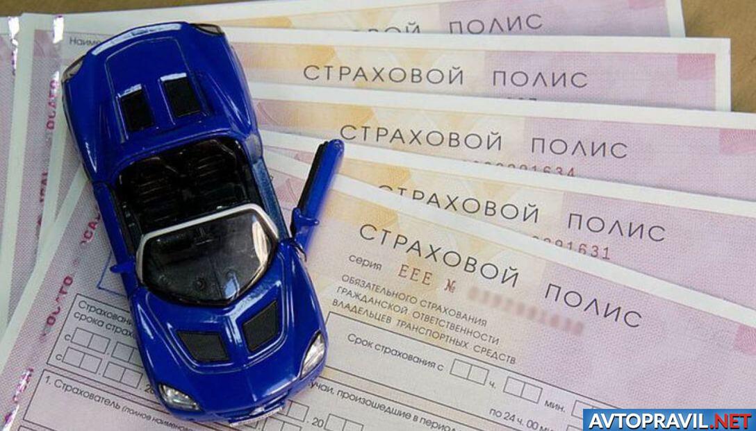 Модель автомобиля, стоящая на бланках страховых полисов