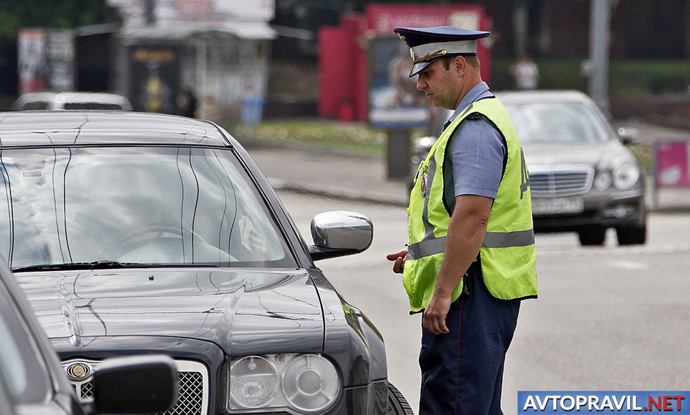 Сотрудник ДПС, стоящий рядом с автомобилем