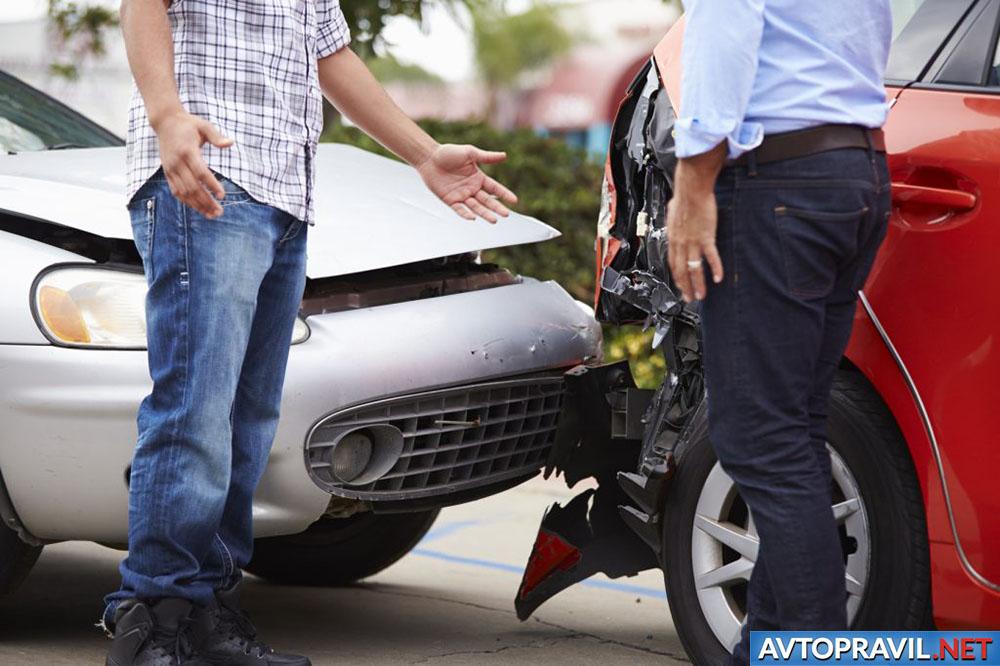 Двое мужчин, стоящие возле разбитых автомобилей