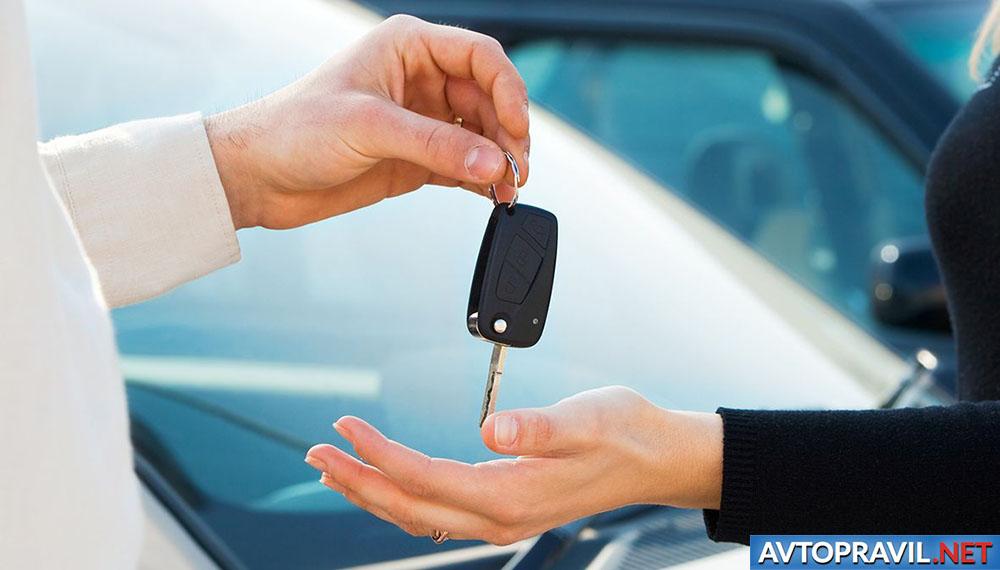 Мужчина, передающий женщине ключи от авто