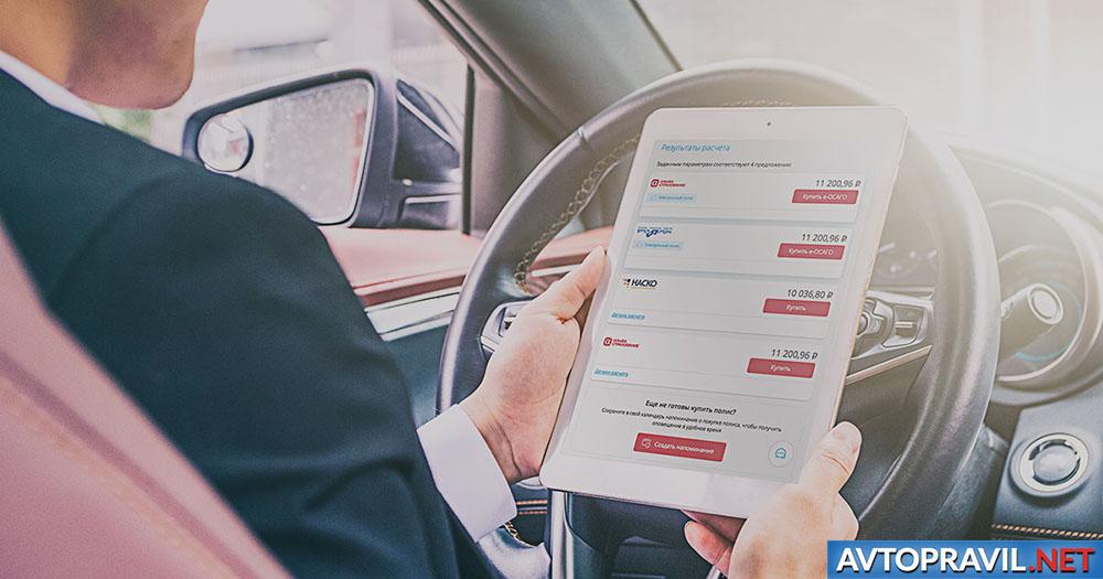 Мужчина в автомобиле, держащий планшет в руках