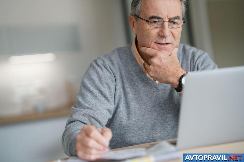Мужчина, сидящий за столом с ноутбуком