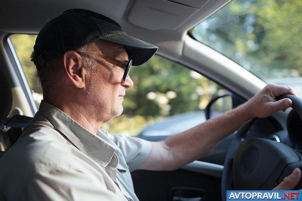Пожилой мужчина за рулем автомобиля