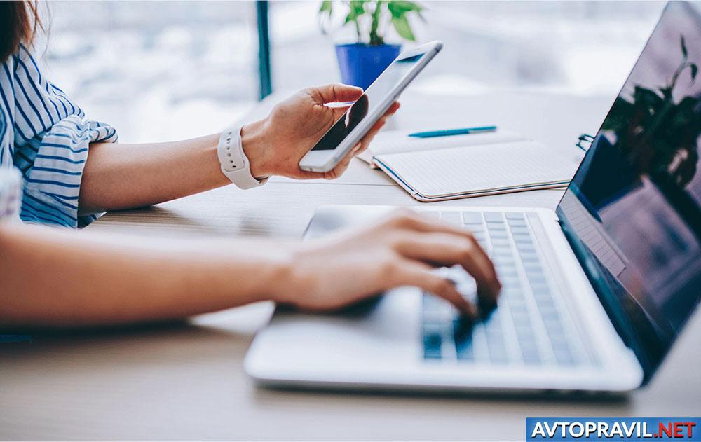 Девушка с телефоном в руках, работающая за ноутбуком