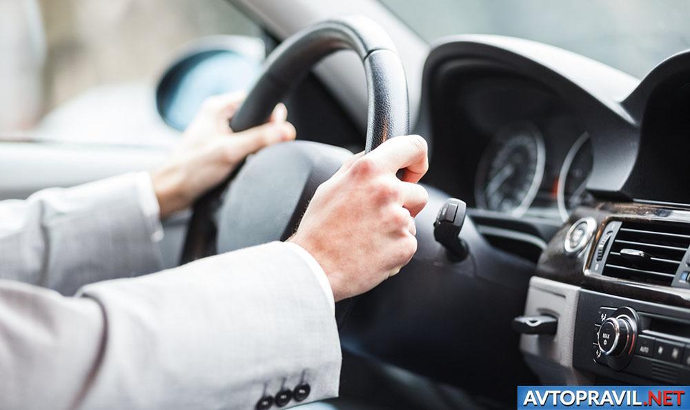 Мужчина, держащийся за руль автомобиля