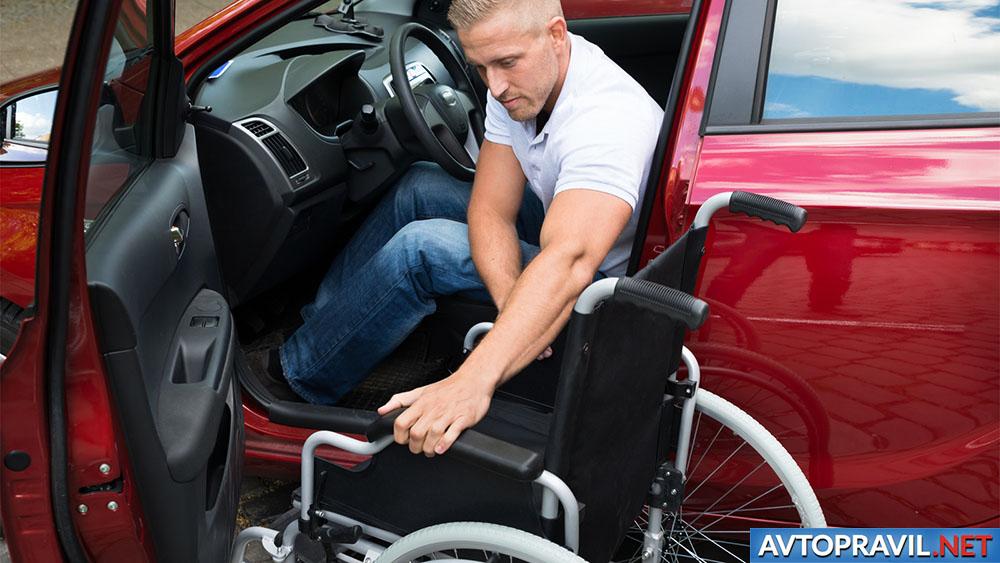 Инвалид, пересаживающийся из автомобиля в инвалидное кресло