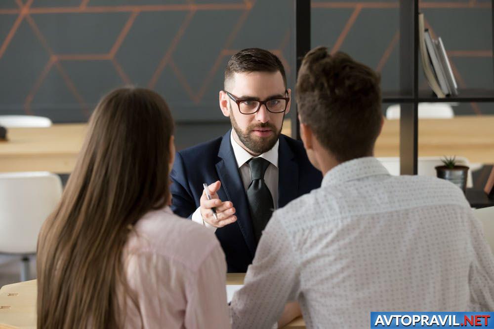 Страховой агент и клиенты, сидящие за столом