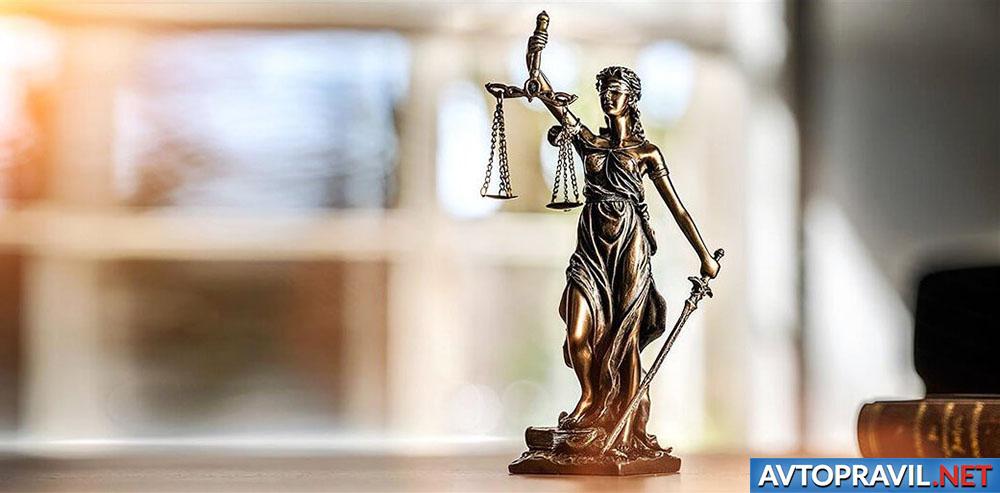 Статуя справдливости, стоящая на столе