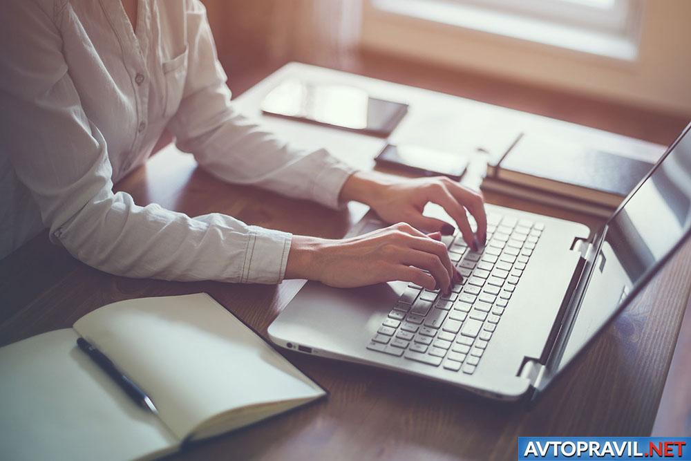 Девушка сидящая за столом с ноутбуком