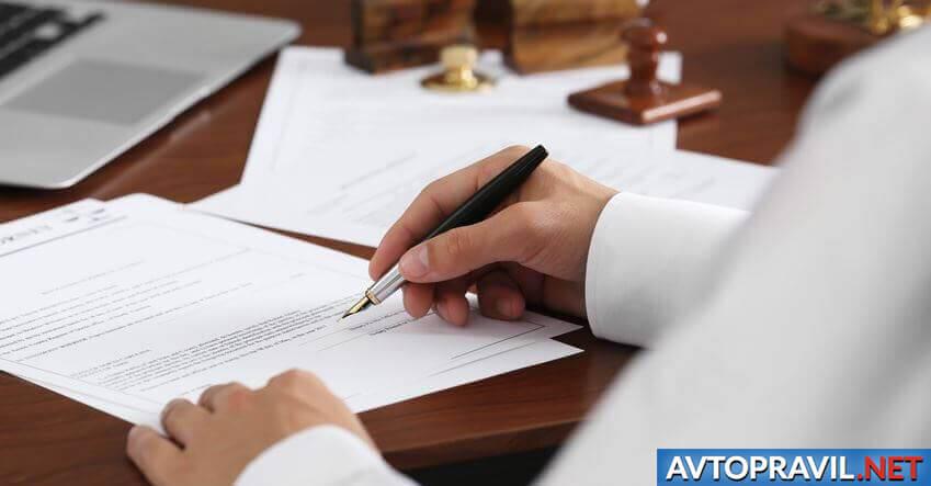 Перо в мужской руке над документами
