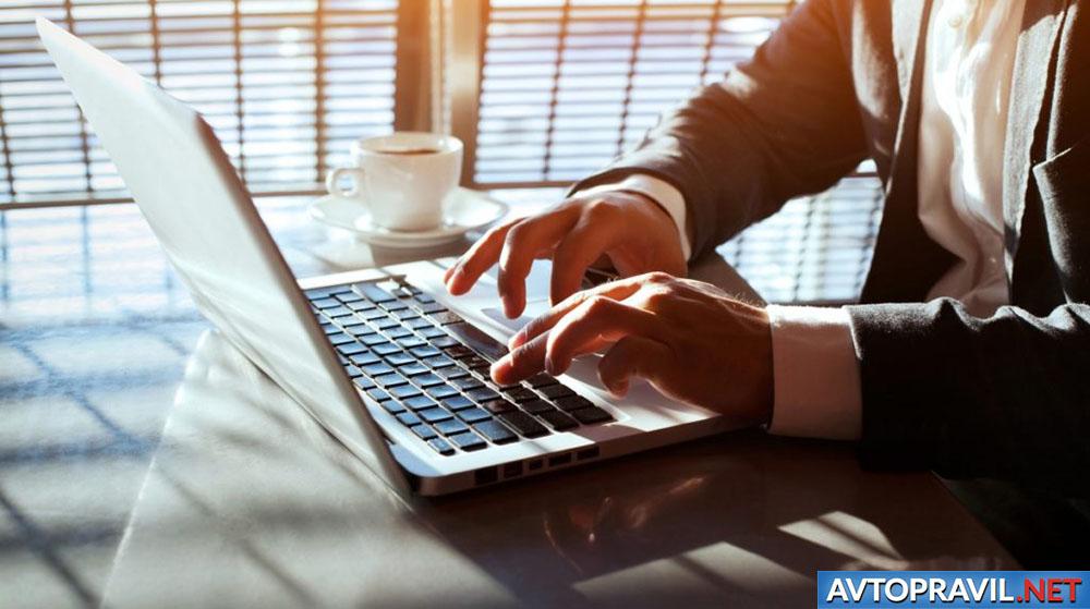 Мужчина, сидящий за ноутбуком с чашкой кофе